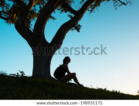 Woman traveler with backpack resting under the tree. - stock photo