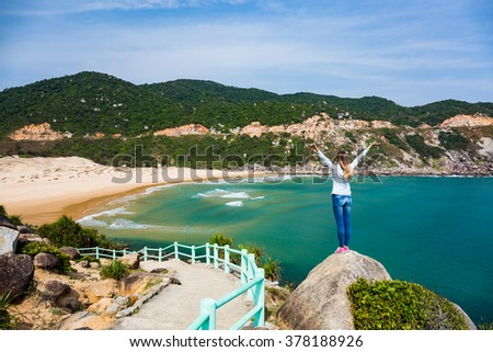 Woman traveler with outspread hands admiring beautiful sea view