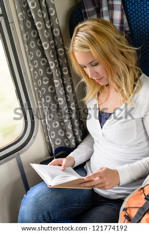 Woman traveling by train and reading book commuter journey sitting - stock photo
