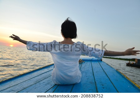 Woman traveling by wood boat at sunset among the islands - stock photo