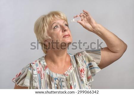 woman treats his eyes medicine - stock photo