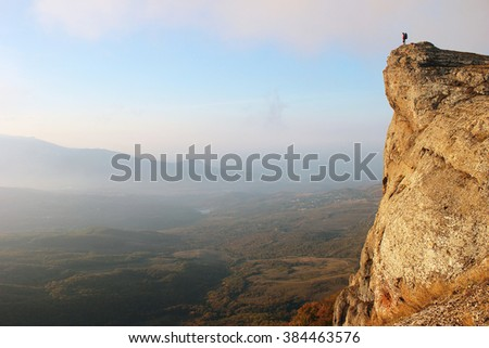 Woman trekker stands on edge of the cliff looking over misty valley - stock photo