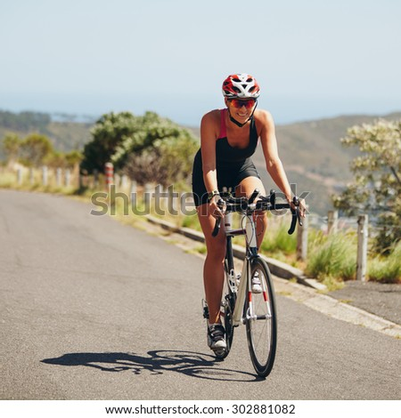 Woman triathlon athlete cyclist down hill on country road. Young woman riding bicycle on open road, practicing for triathlon competition. - stock photo