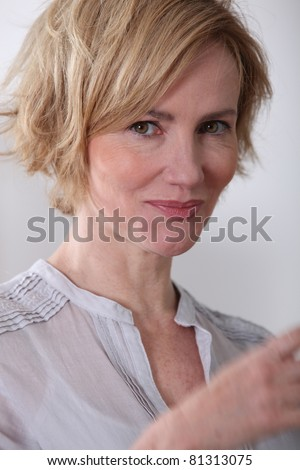 Woman trying not to laugh. - stock photo
