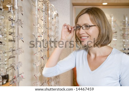 Woman trying on eyeglasses at optometrists smiling - stock photo