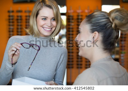 Woman trying on glasses with optician - stock photo