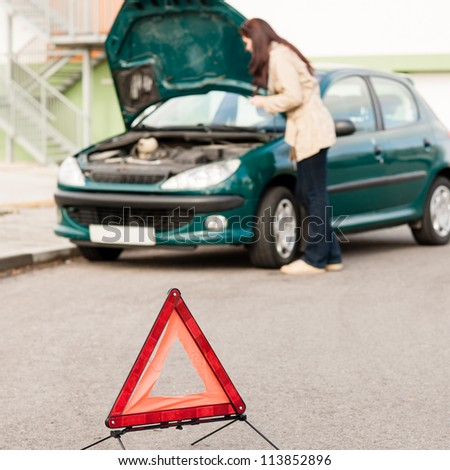 Woman trying to fix her broken car breakdown sign triangle - stock photo