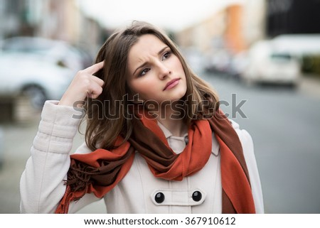 Woman trying to remember Closeup portrait headshot  young lady girl scratching head thinking daydreaming deeply about something looking up isolated cityscape outdoor background Multicultural mixt race - stock photo