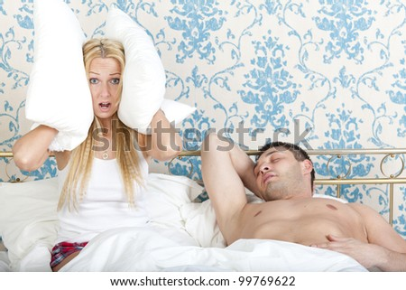 Woman trying to sleep while man snoring - stock photo