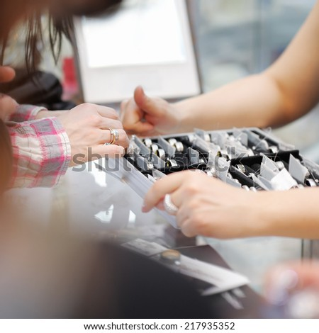 Woman trying wedding rings at a jeweller, focus on hand