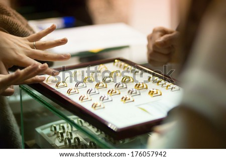 Woman trying wedding rings at a jeweller, focus on rings - stock photo