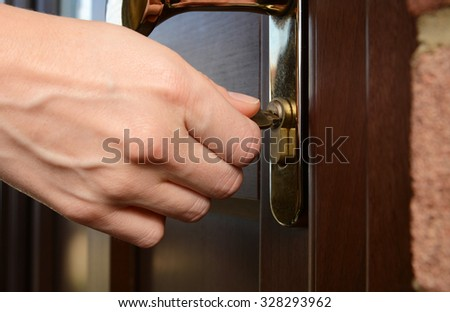 Woman turns the key in a lock on an external door - stock photo