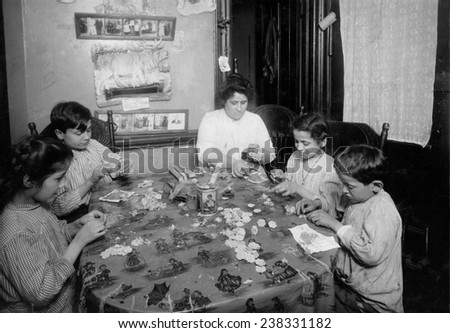 Woman, two boys, and two girls sitting at a table, making artificial flowers, New York City, photograph by Lewis Wickes Hine, March, 1922