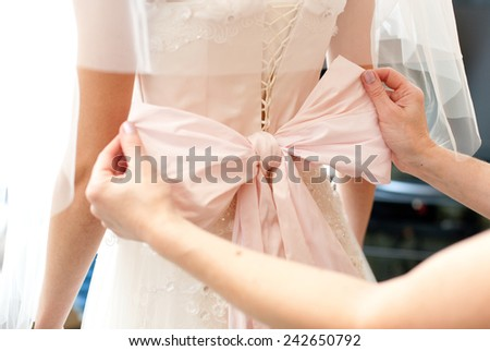 Woman tying a pink bow tie on a wedding dress - stock photo