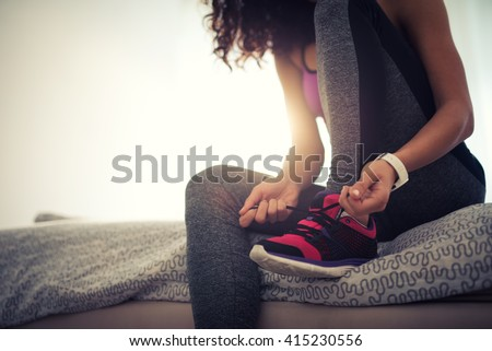 Woman tying a shoelace and preparing for fitness. - stock photo