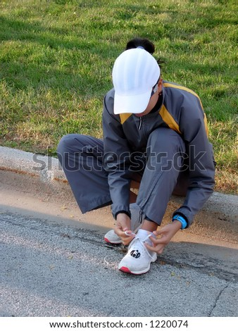 Woman tying shoes before a race