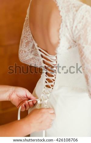 woman tying wedding dress on bride - stock photo