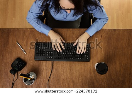 woman typing and working hard at her desk taken from a birds eye view - stock photo