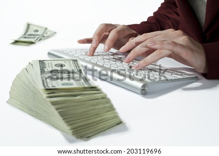 Woman typing at the stack of banknote - stock photo