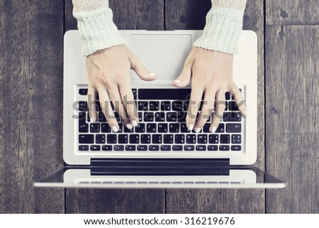 Woman typing on a laptop - stock photo