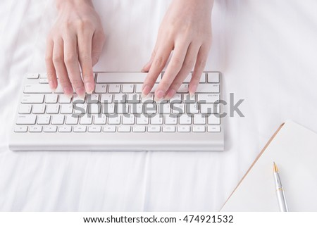 woman typing on computer keyboard, Low light, selective focus on hand, can be used for e-commerce, business, technology and internet concept.
