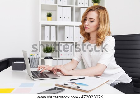 Woman typing on her laptop keyboard in big city room. Clipboard and office supplies lie on table. Concept of secretary work.