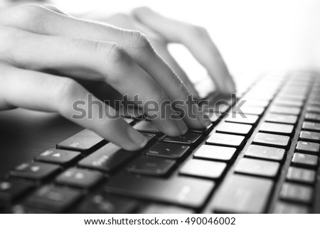 Woman typing on laptop, black and white photography