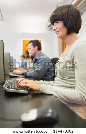 Woman typing on the computer in the class - stock photo