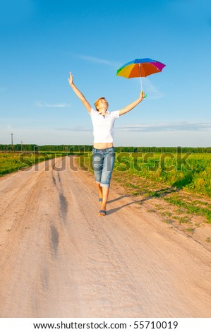 woman under blue sky with umbrella in field