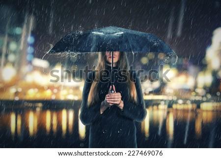 Woman under rain with black umbrella - stock photo