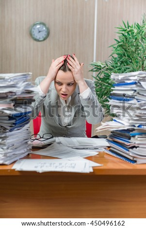 Woman under stress from excessive paper work - stock photo