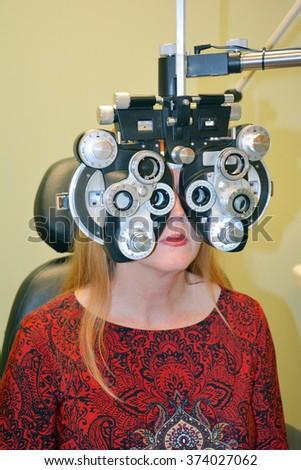 Woman undergoing refractive eye exam. - stock photo