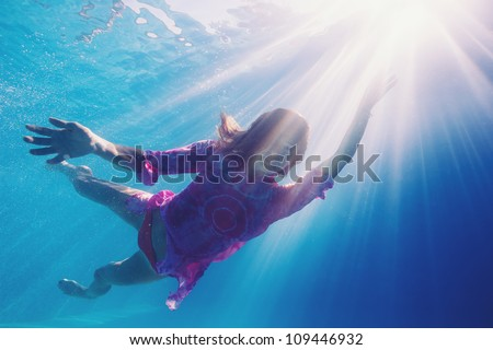 Woman underwater in swimming pool with back light. - stock photo