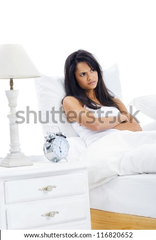 Woman unhappy to wake up early is reluctant to get out of bed isolated on white background - stock photo
