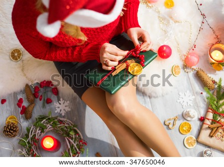 Woman unwrapping Christmas gifts - stock photo