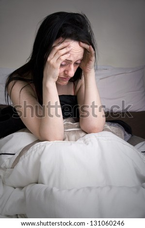 woman upset, crying lying in bed in bedroom portrait with copy space - stock photo