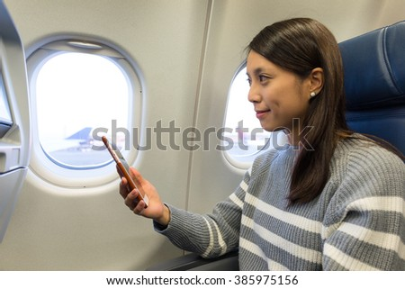 Woman use mobile phone and looking out of the window at plane cabin - stock photo