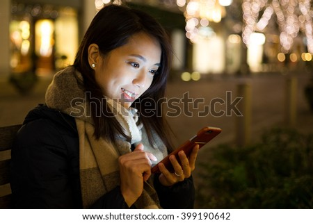 Woman use mobile phone in city at night - stock photo