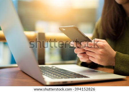 Woman use of cellphone and laptop computer - stock photo