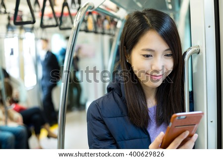 Woman use of cellphone inside train compartment - stock photo