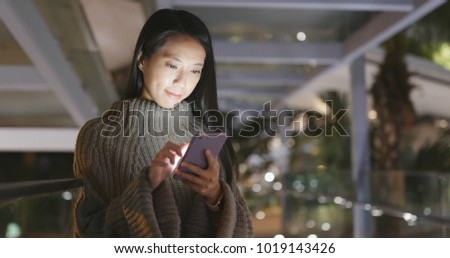 Woman use of mobile phone cityscape