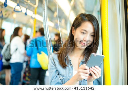 Woman use of mobile phone inside train compartment - stock photo