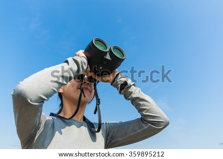 Woman use of the binoculars for looking up