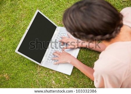Woman uses a laptop while lying on her front in grass