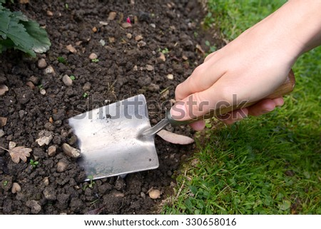 Woman uses a metal hand trowel to dig in the soil of her garden flower bed - stock photo