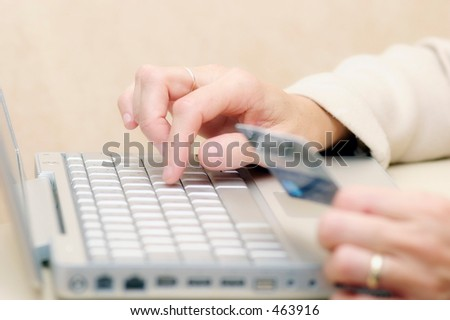 Woman using a credit card to buy goods online - stock photo