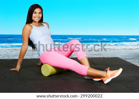 Woman using a foam roller after a workout - stock photo