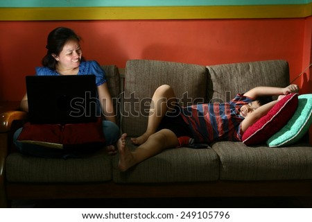 Woman using a laptop computer and Young kid smartphone on couch Photo of tablet or