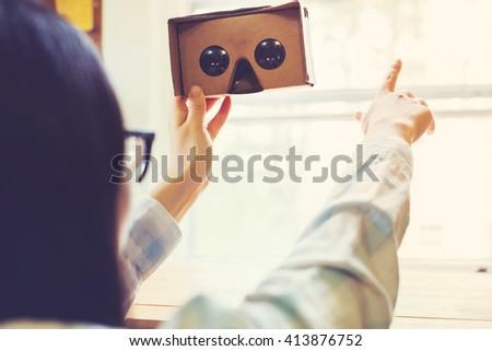 Woman using a new virtual reality headset - stock photo