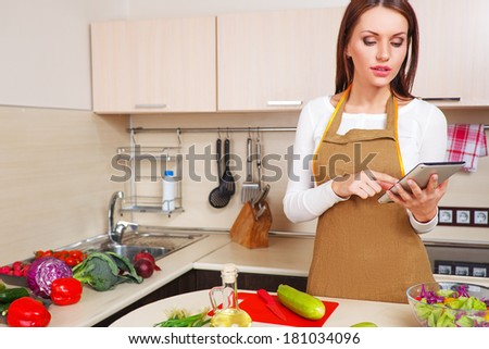 woman using a tablet computer to cook in her kitchen - stock photo